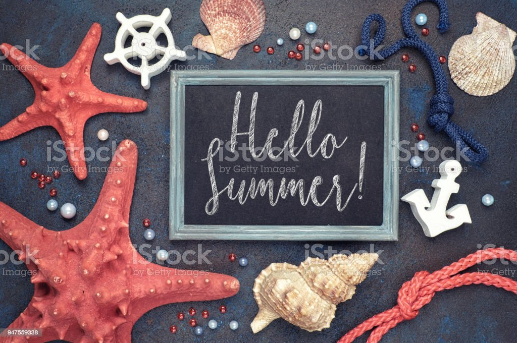 Blackboard with 'Hello Summer!' chalk text, with sea shells, rope and star fish on dark blue stock photo