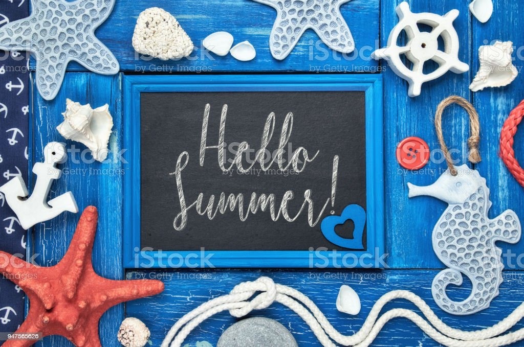 Blackboard with 'Hello Summer!' chalk text, with sea shells, stones, rope and star fish on blue wood stock photo