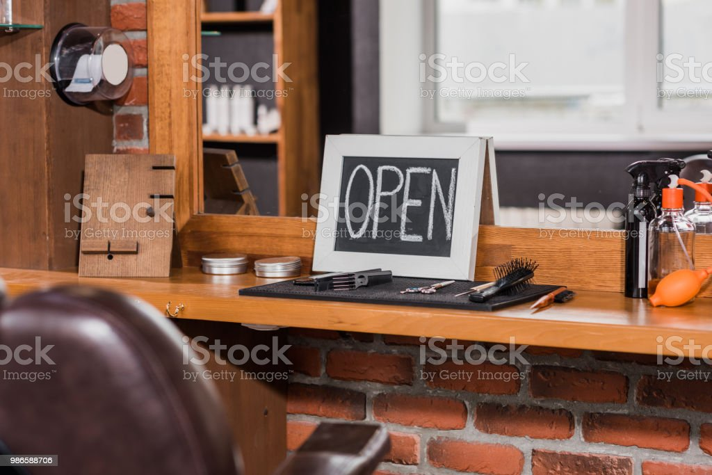 blackboard with open sign leaning on mirror at barbershop stock photo