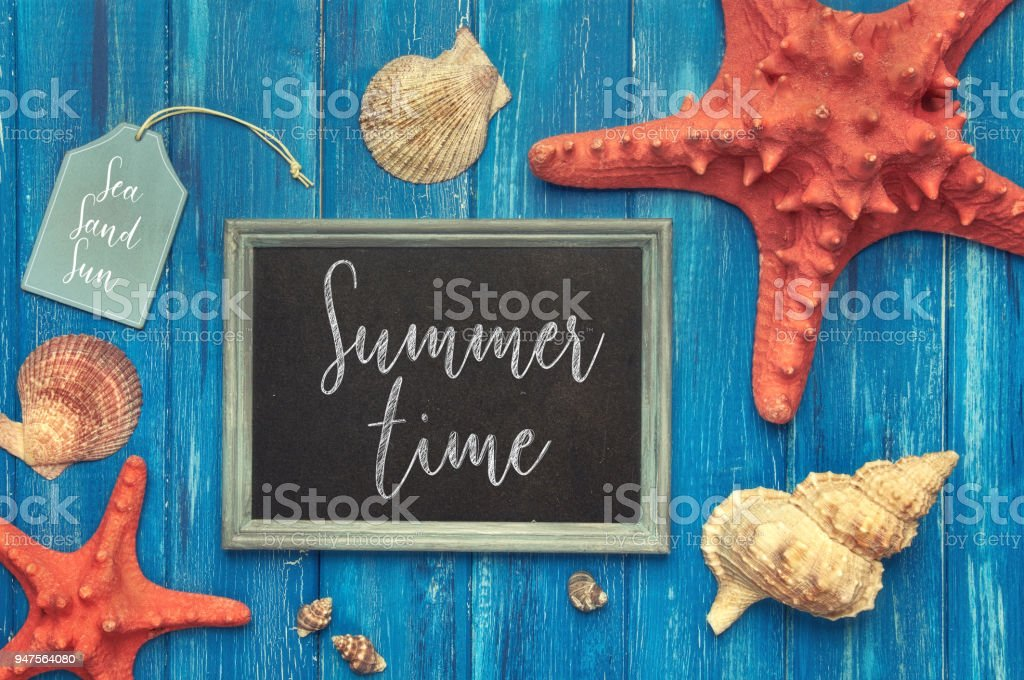 Blackboard with 'Summer time' chalk text, with sea shells, rope and star fish on blue  wood stock photo