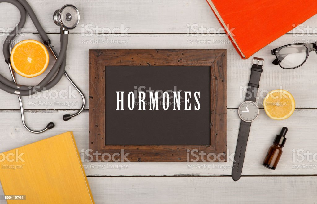 blackboard with text 'Hormones', books, stethoscope and watch stock photo