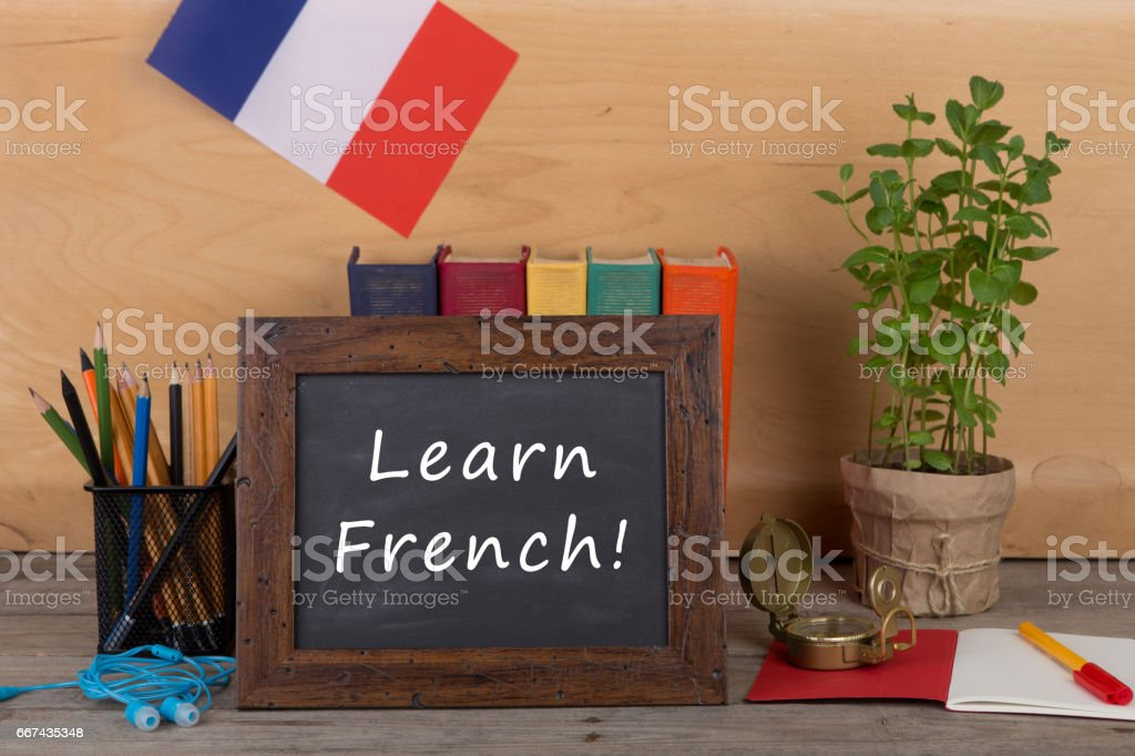 blackboard with text 'Learn French!', flag of the France stock photo
