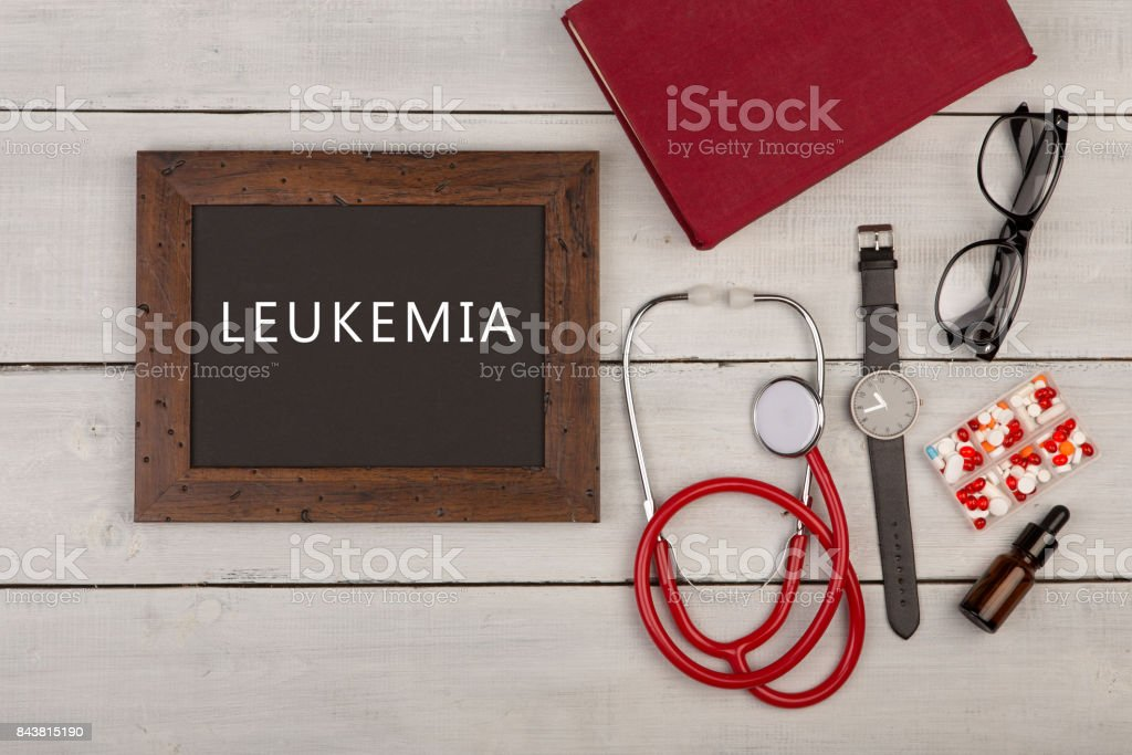 blackboard with text 'Leukemia', pills, book, eyeglasses, watch and stethoscope stock photo