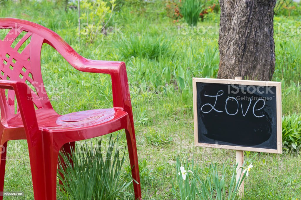 blackboard with text 'love' on the grass and red chair royalty-free stock photo