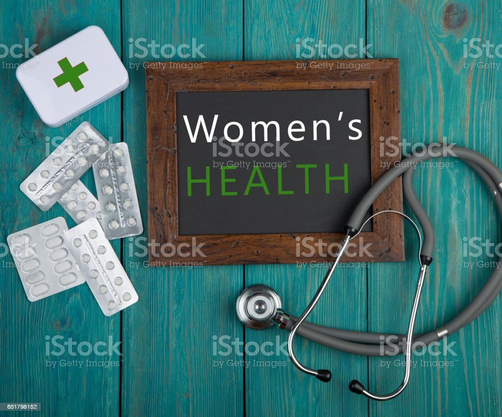 Blackboard with text 'Women's health', stethoscope, pills stock photo