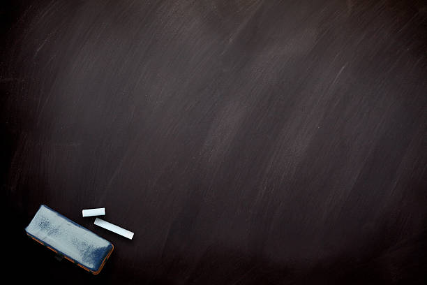Blackboard with white chalks and eraser. Horizontal composition stock photo