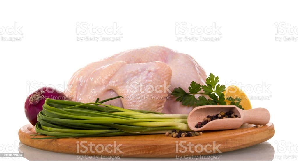 Blackboard with whole raw chicken carcass, scoop with pepper, onion, parsley and lemon portion isolated on white. stock photo