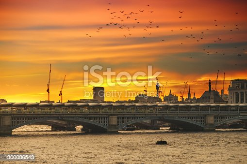 Blackfriars Bridge over the Thames River in London under the red sky at sunset, city skyline in the background with construction cranes rising between