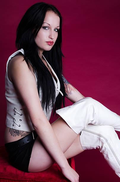 Blackhaired modelo em couro branco e colete de botas. - foto de acervo