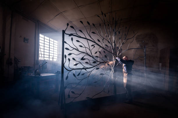 Blacksmith artist working in his smithy studio creating a gate-tree stock photo