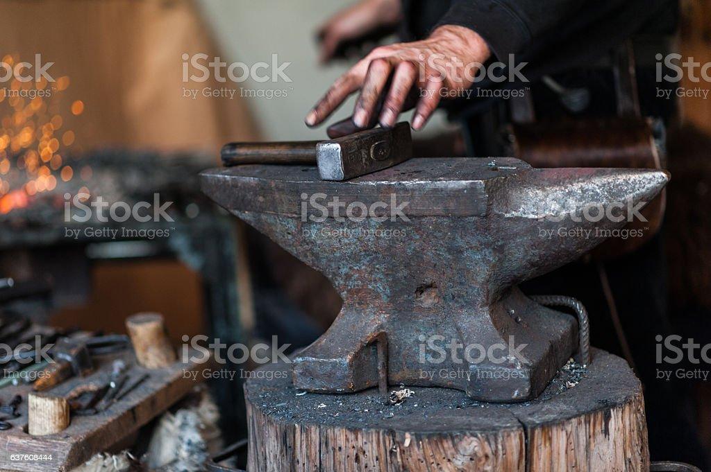 Blacksmith at the workshop. stock photo