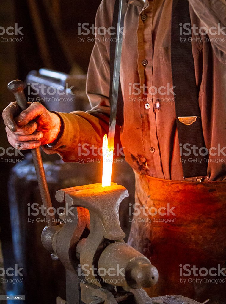 Blacksmith bending a hot metal rod stock photo