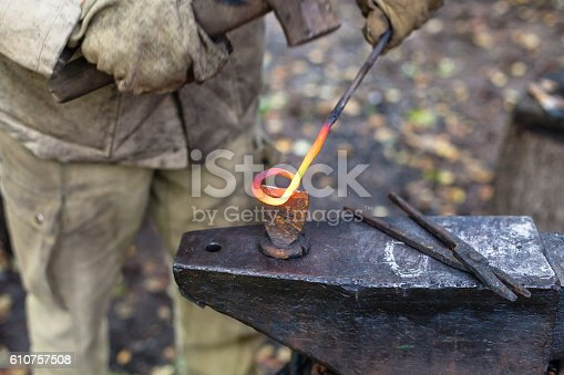 547224670istockphoto Blacksmith cut out a buckle with hammer and chisel 610757508
