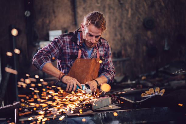 Blacksmith cutting metal with angle grinder in workshop stock photo
