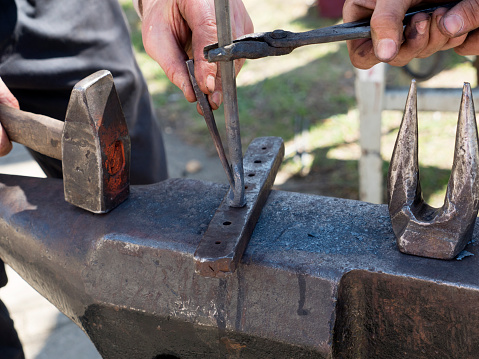 istock Blacksmith forge with hammer iron on anvil 954219780