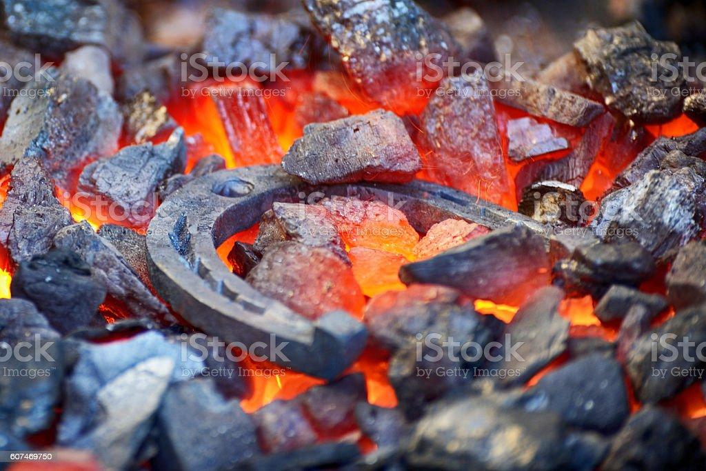 Blacksmith forges a horseshoe stock photo