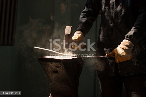 547224670istockphoto blacksmith forging a iron bar on anvil block 1149881261