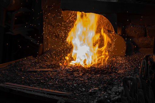 547224670 istock photo Blacksmith forging iron in workshop 1128750341