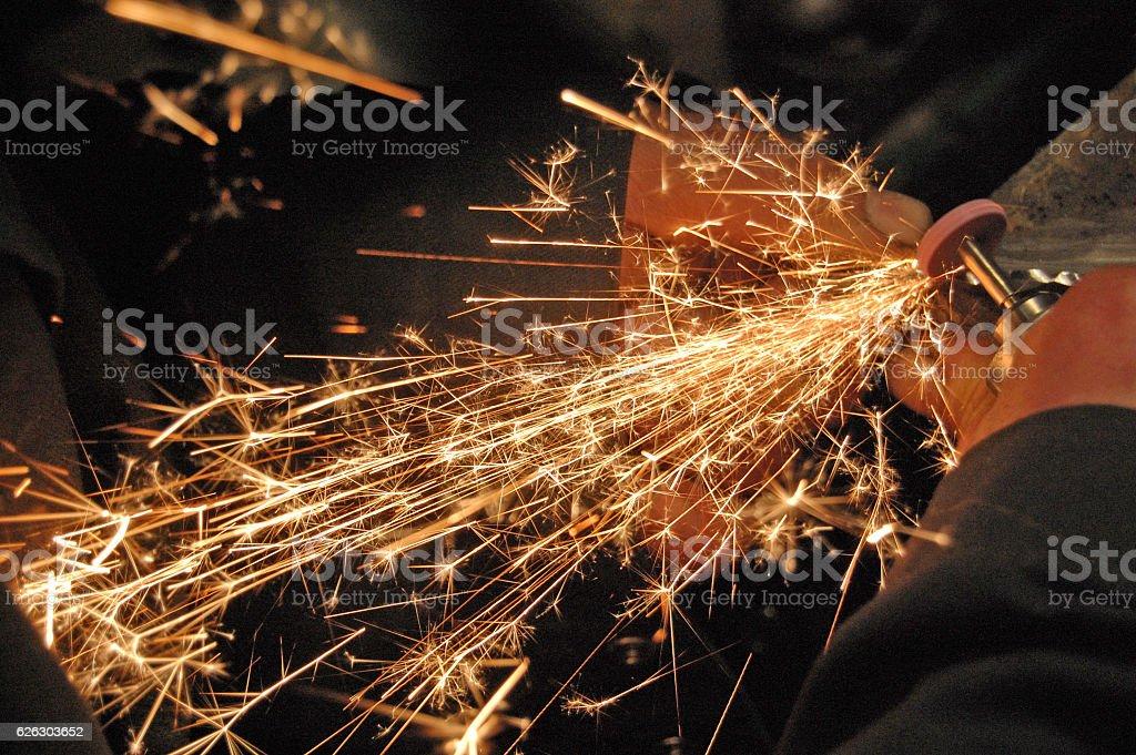 Blacksmith grinding detail at his workshop.  Image full of sparkles stock photo