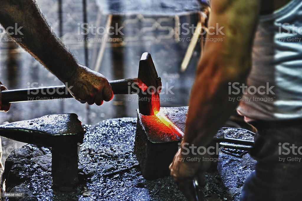 Blacksmith hammering a hot metal rod stock photo