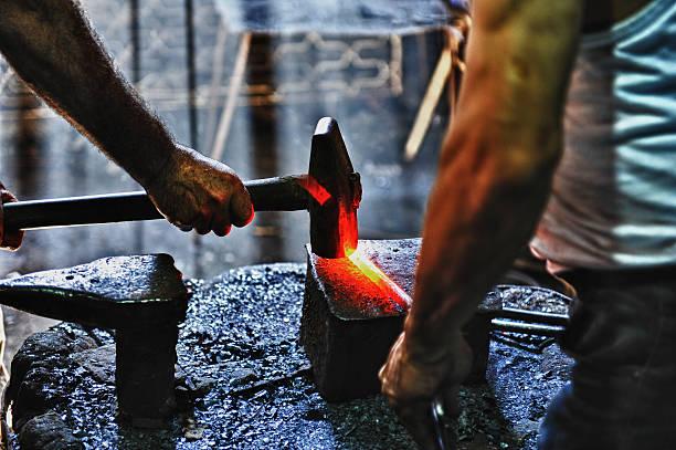 blacksmith hammering a hot metal rod - hovslagare bildbanksfoton och bilder