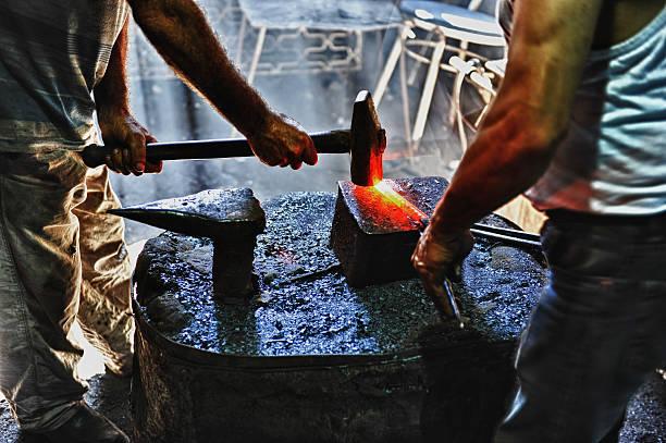 Blacksmith hammering a hot metal rod Blacksmith hammering a hot metal rod anvil stock pictures, royalty-free photos & images