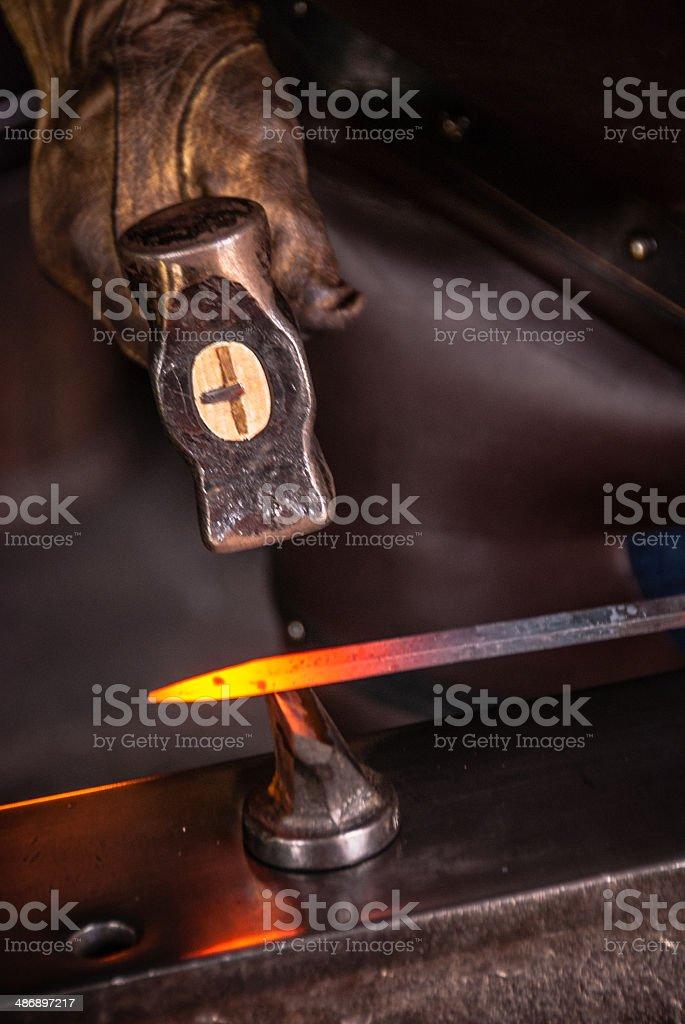 Blacksmith hammering a hot piece of metal stock photo