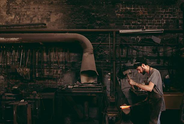 blacksmith hammering glowing iron on anvil in workshop - hovslagare bildbanksfoton och bilder