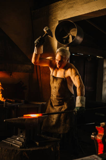 Blacksmith hammering glowing iron on anvil in workshop Blacksmith hammering glowing iron on anvil in workshop anvil stock pictures, royalty-free photos & images