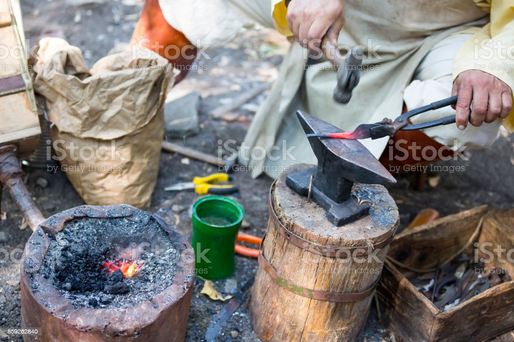 Blacksmith hammering hot metal arrow stock photo