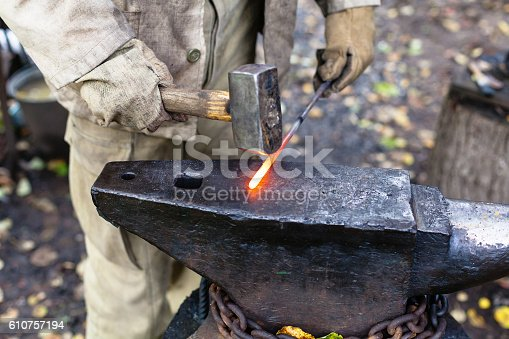 547224670istockphoto Blacksmith hammering hot steel rod on anvil 610757194
