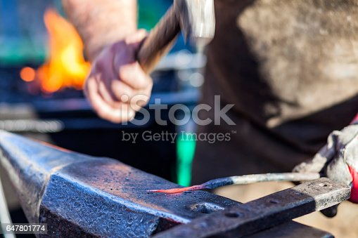 istock Blacksmith hammering iron rod on anvil in background fire 647801774
