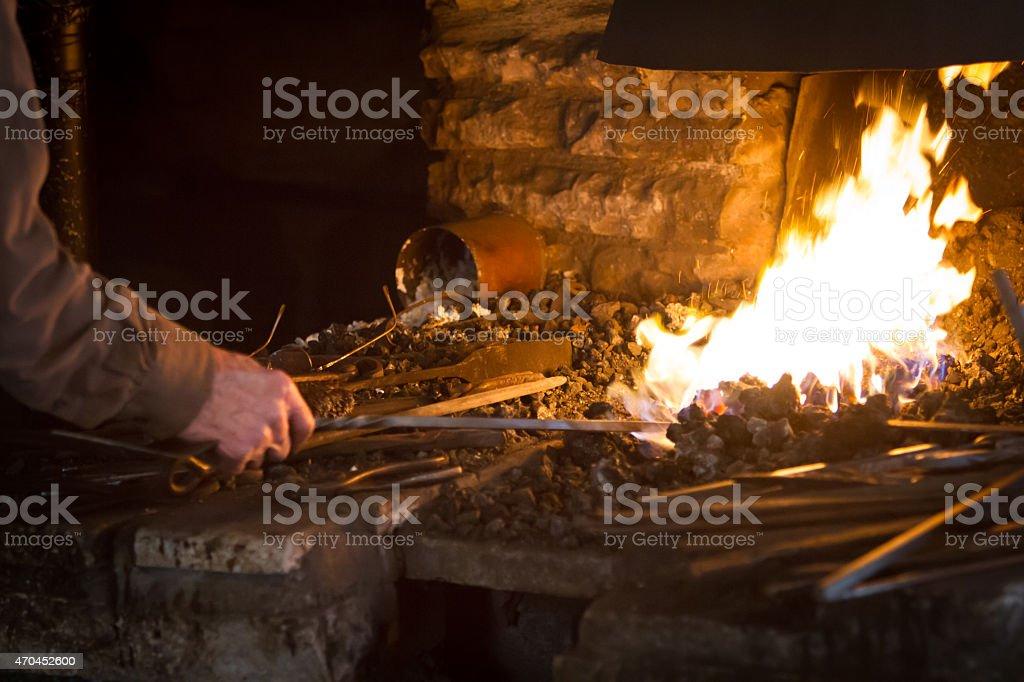 Blacksmith heating a metal rod stock photo