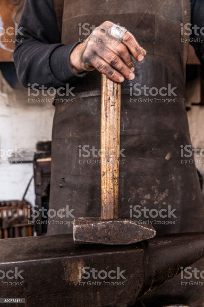Blacksmith Holding a Iron Hammer on Anvil stock photo