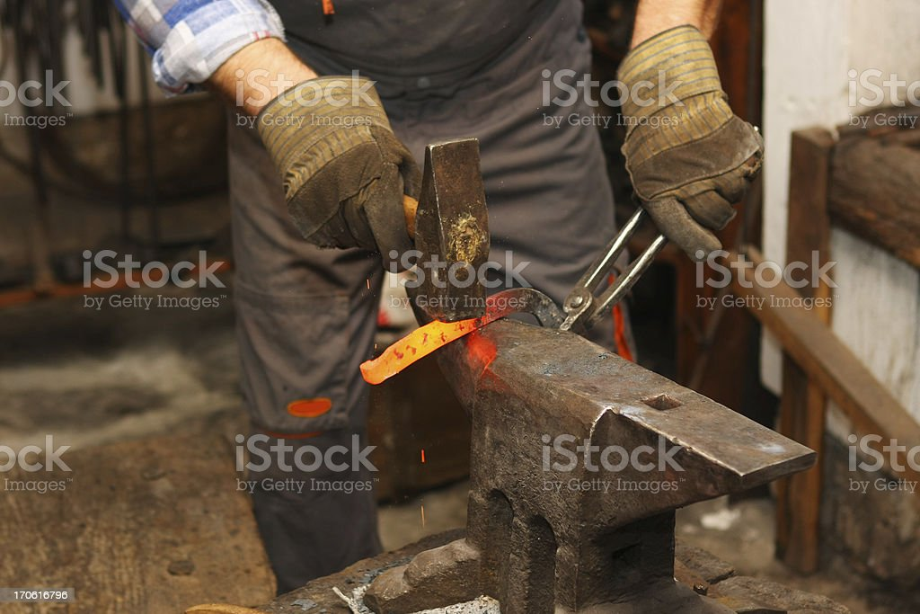 Blacksmith is hammering a red hot piece of iron royalty-free stock photo
