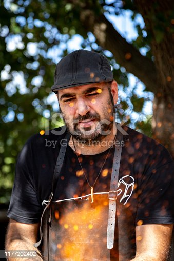 Blacksmith looking at the embers of the forge. Concept of concentration and care at work
