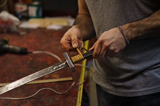 istock Blacksmith makes leather winding sword 957121426