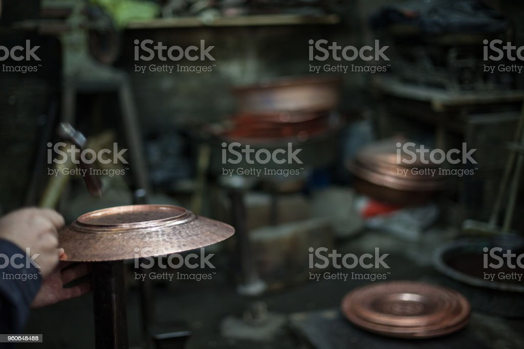 Close up photo of blacksmith making copper craft product with hammer....