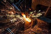 istock Blacksmith manually forging the molten metal on the anvil with spark fireworks 1221240454