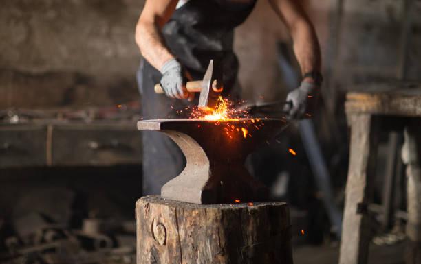 Blacksmith manually forging the molten metal stock photo