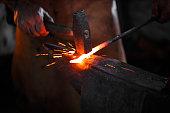 istock Blacksmith manually forging the molten metal 607898530