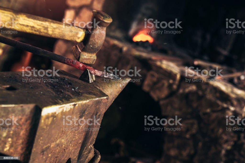 Blacksmith manually forging the molten metal - stock photo