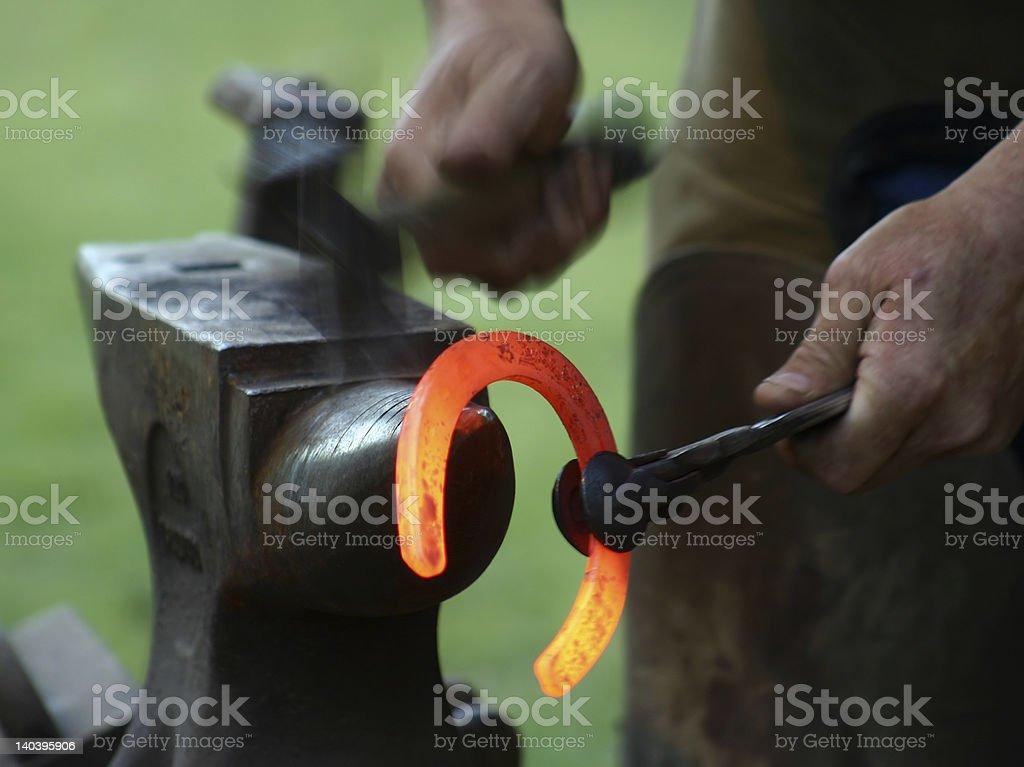 Blacksmith molding glowing horse shoe royalty-free stock photo