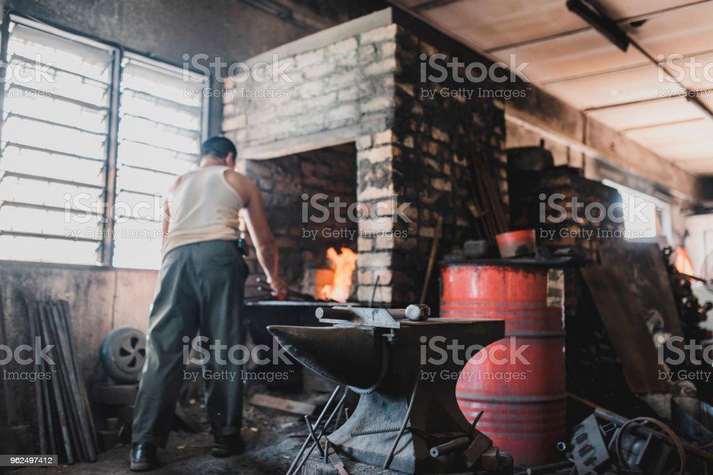 Blacksmith preparing to work in his metal workshop stock photo