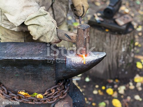 547224670istockphoto Blacksmith processing red hot iron rod on anvil 610757226