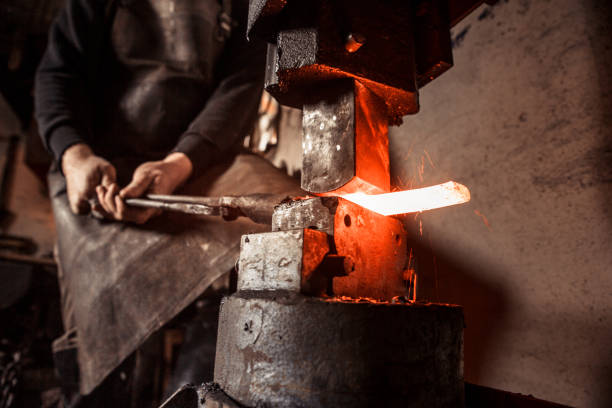 Blacksmith Shaping a Piece of Iron with Hydraulic Press Machine Blacksmith Shaping a Piece of Iron with Hydraulic Press Machine in his Workshop metalwork stock pictures, royalty-free photos & images