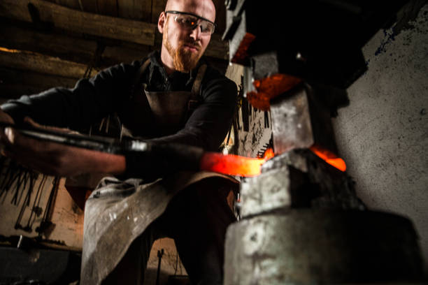 Blacksmith Shaping a Piece of Iron with Hydraulic Press Machine stock photo