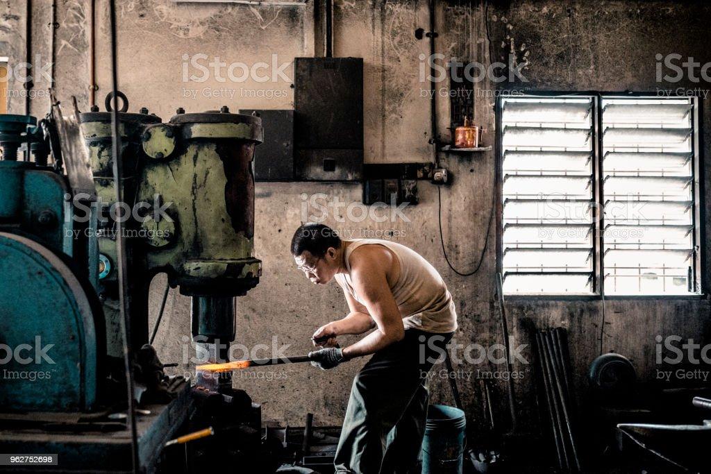 Ferreiro, dando forma a um pedaço de ferro com máquina de prensa hidráulica - Foto de stock de 30 Anos royalty-free