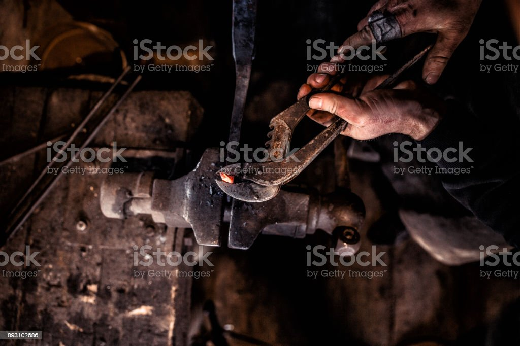 Blacksmith Shaping Metal Head Of Ram Using The Forge Tongs stock photo
