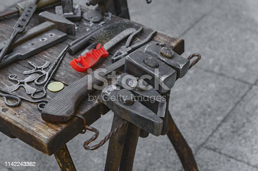 547224670istockphoto blacksmith tools and workplace: anvil, hammers, blacksmith tongs, firesteel. 1142243362
